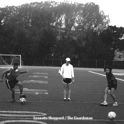 Women's soccer Coach Cunningham lead players Matesha Cheatham (left) and Monica D'Amario (right) in practice drills. LYNNETTE SHEPPARD / GUARDSMAN