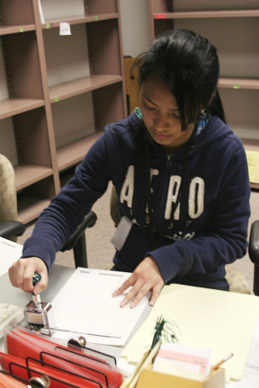 Student worker Avonn Meja stamps forms in her clerical job for the Rosenberg Library. PHOTO BY GRACIE MALLEY