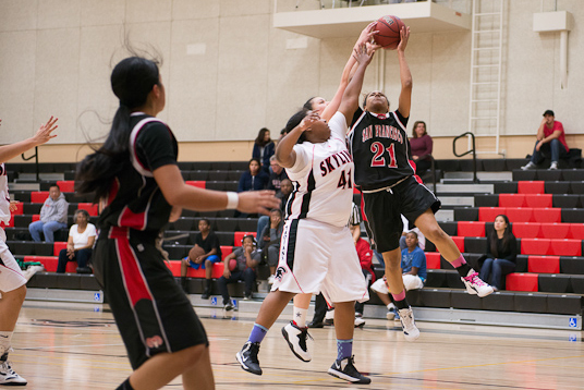 Ram's Olivia Overtone-Mayorga (21) takes a shot at the hoop against the Trojans at Skyline College on Feb. 15. (Clarivel Fong / The Guardsman)
