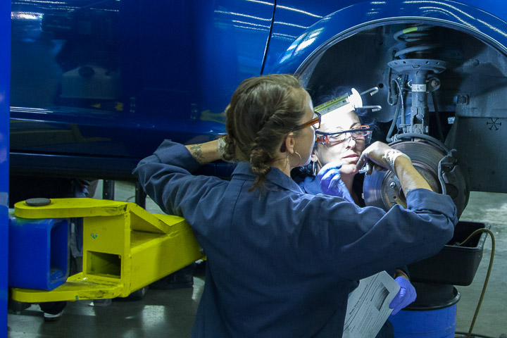 Mrs. Lisa Duke(left) Automitive mechanics instructor shows Lucia Mampieri how to measure the brake pads on a car. Photo by JuanPardo/The Guardsman