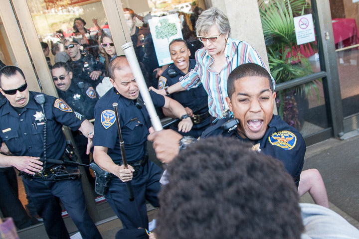 SFPD officer brandishes his baton attempting to stop City College students from entering Conlan Hall during a protest on Thursday, March 13, 2014. Over 15 students forced entry and staged an overnight sit in. Photo by Santiago Mejia/The Guardsman