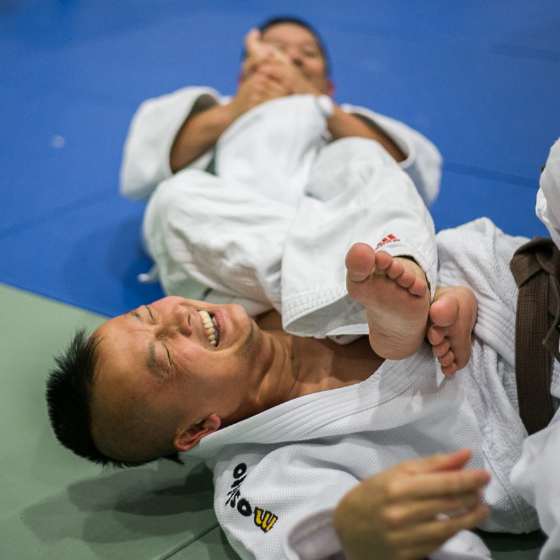 Astronomy Department Chair Lancealot Kao, bottom, reacts as he's put into an armbar during practice at the Ocean campus Wellness Center, Tuesday, April 29, 2014. Photo by Elisa Parrino/The Guardsman