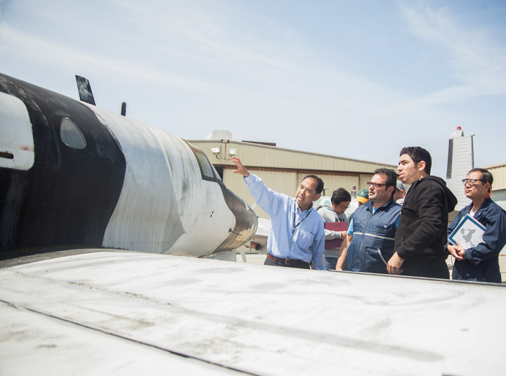 Instructor Hoi Ko, left, gestures to the Sabreliner T-39 aircraft and lectures his students on its components.