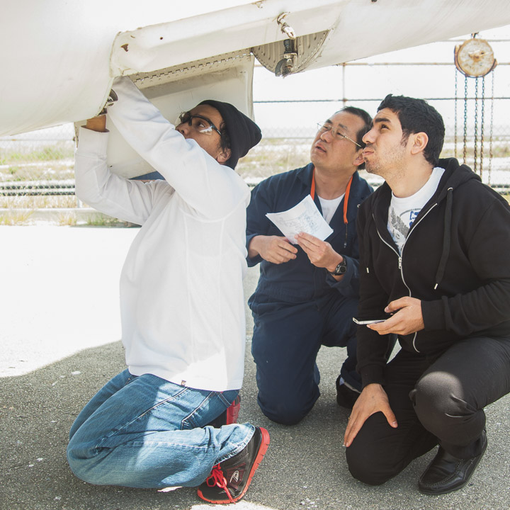 (L-R) Students Aries Gerald Pangan, 21, Peter Yuthrayard, 43, and Kerols Shafik, 25, inspect the Sabreliner T-39 air conditioning bay.