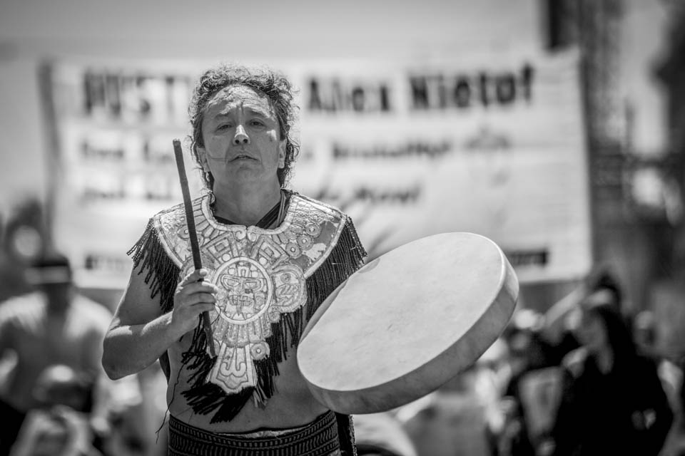 Louie Gutierrez leads the Saturday, Aug. 22 march in honor of Alejandro Nieto with his Aztec dance group Coyolxauqi down Van Ness Avenue. (Photo by Nathaniel Y. Downes)