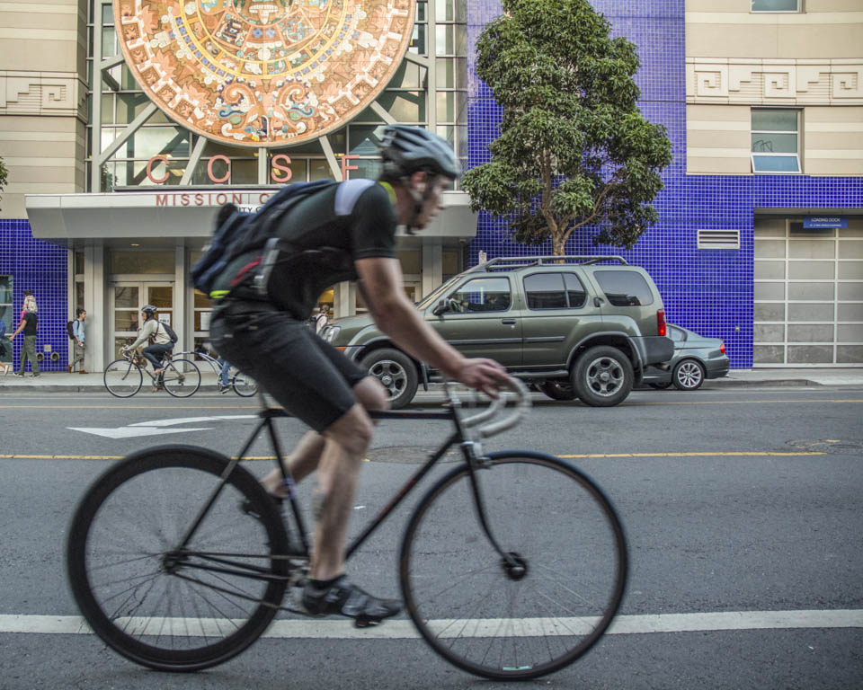 A cyclist rides past the City College Mission Center, Thursday, Sept. 25. (Photo by Niko Plagakis)