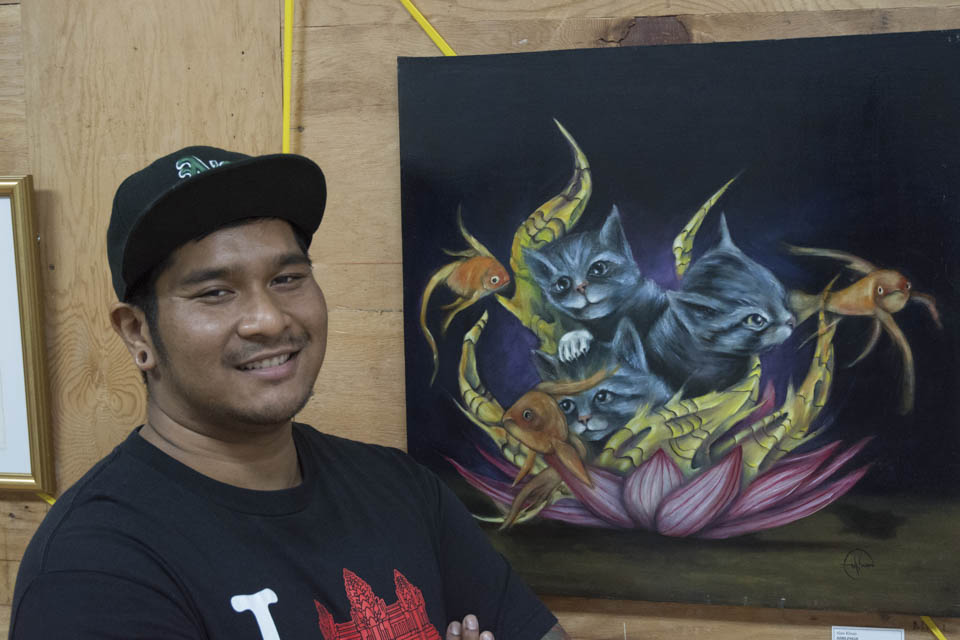 """Alan Khum, San Francisco resident, artist and collaborator with Inks of Truth, stands in front of one of his pieces on display as part of the 2 Blocks Art Walk at the old San Francisco Barber College located at 64 6th Street, San Francisco. """"This is my second time showing my work with Inks of Truth,"""" He stated on Friday, Oct. 10. (Photo By: Niko Plagakis)"""