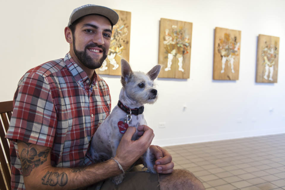 David Polka sits with his dog during the opening reception of his art exhibition at the City College Art Gallery, Thursday, Oct. 2. (Photo by Nathaniel Y. Downes)