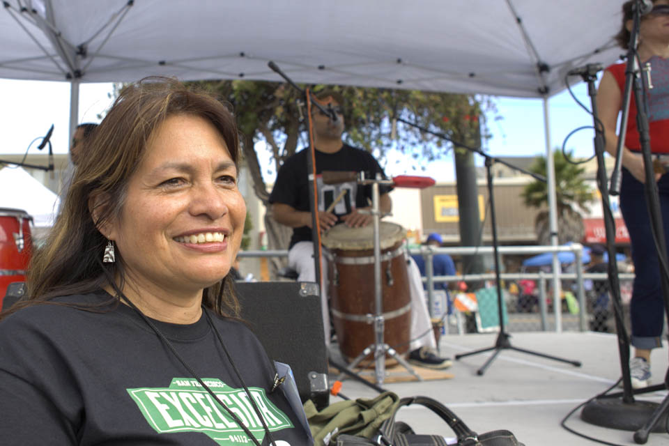 A City College alumni and the music coordinator of 12th Annual Excelsior Art & Music Festival, Rosario Cervantes, stands in front of the music stage while Puerto Rican music band 'La Mixta Criolla' performs at the Sunday Streets Festival in The Excelsior, San Francisco on Sunday, Sept. 28, 2014. Each year Sunday Streets collaborates with the Excelsior Art & Music Festival to bring fun activities to the community. (Photo by Ekevara Kitpowsong)