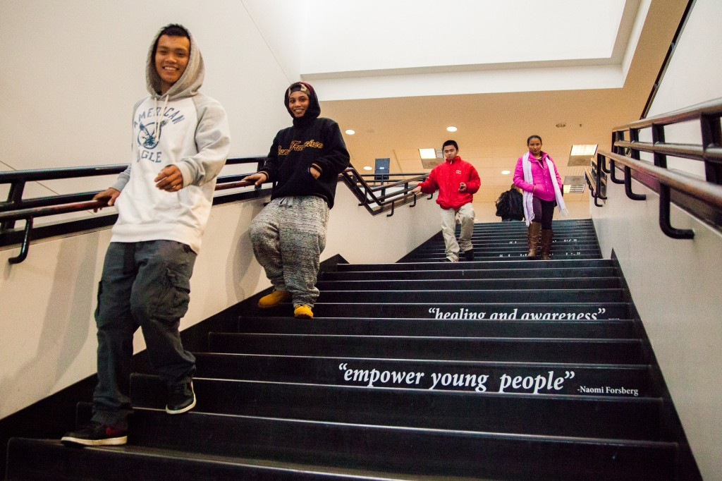 Students descend the stairs of the Rosenberg Library where excerpts from Project SURVIVE's testimonials are displayed. (Photo by Ekevara Kitpowsong)