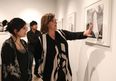 """Amanda Aceves, left, and Photography Department Chair, Erika Gentry, right, view the photographs displayed during the opening reception of """"Dreamscapes,"""" exhibition by Amanda Aceves at Gallery Obscura at Ocean Campus, Monday, Feb. 9. (Photo by Natasha Dangond)"""