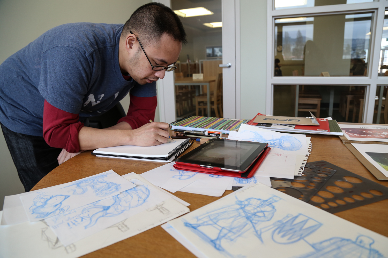 Illustrator Anthony Mata sketches original artwork at the City College Mission Center Library on Tuesday, March 10. (Photo by Natasha Dangond)