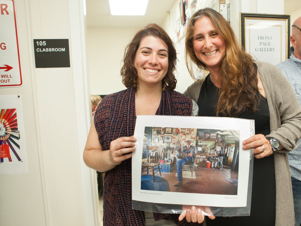 "(L-R) Sara Bloomberg, former editor-in-chief of The Guardsman, won a photograph by Jessica Lifland from the raffle during the opening reception for ""Faces of Hope"" at Front Page Gallery on Thursday, Sept. 17, 2015. (Photo by Ekevara Kitpowsong/The Guardsman)"