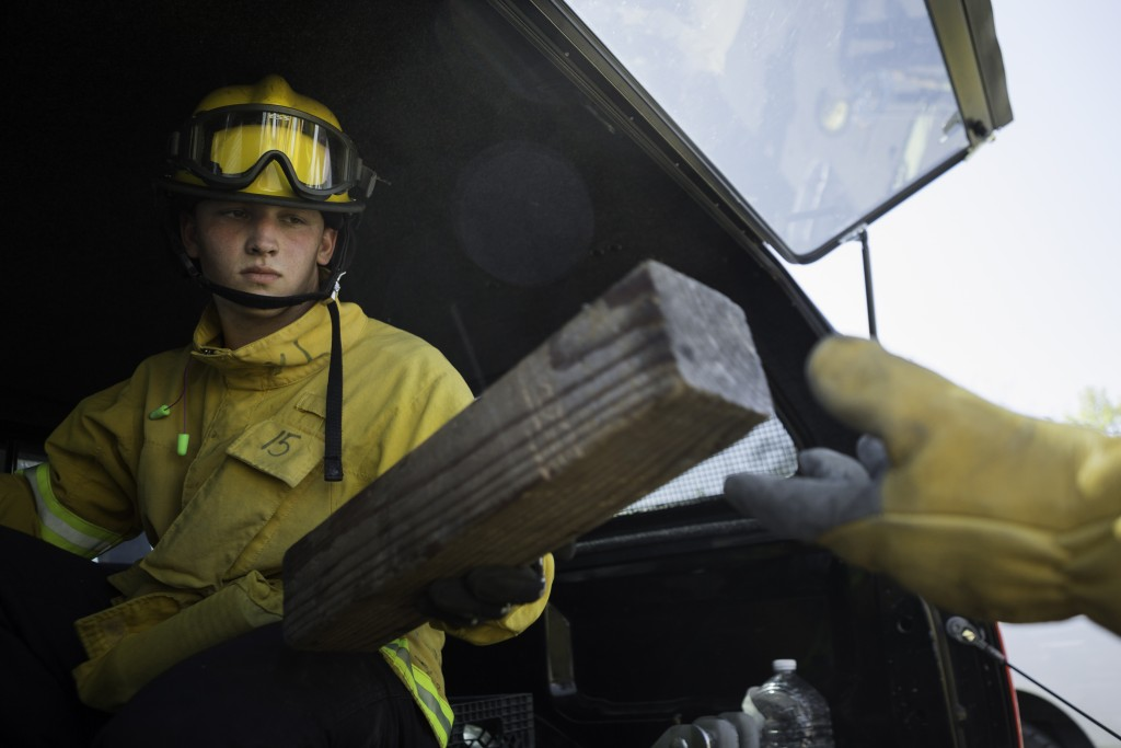 Fire cadet Nick Oatley from City College's Fire Fighter One Academy's Class 15 passes a cribbing used to stabilize and unstable car during the auto extrication training at San Jose Pick and Pull on Saturday, April 18, 2015. (Photo by Nathaniel Y. Downes/The Guardsman)