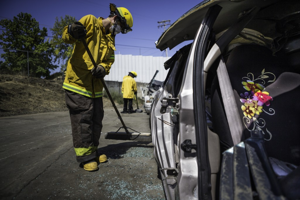 Fire cadet William Scott Cowell from City College's Fire Fighter One Academy's Class 15 cleans up the yard after practicing auto extrication techniques at San Jose Pick and Pull on Saturday, April 18, 2015. (Photo by Nathaniel Y. Downes/The Guardsman)