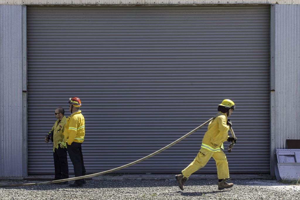 A fire cadet from City College's Fire Fighter One Academy's Class 15 runs a hose during a wlidland training drill while instructors look on at Cal Fire's North Division Fire Station in San Mateo on Saturday, March 28, 2015. (Photo by Nathaniel Y. Downes/The Guardsman)
