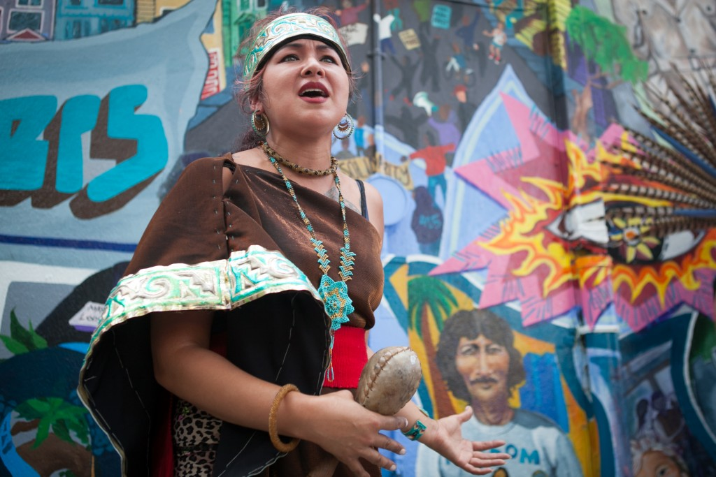 Spiritual traditional dancer Sandra Sandoval of Xiuhcoatl Danza Azteca speaks to the crowd during the celebration of the mural project, at the corner of 24th and Folsom streets on Saturday, Aug. 8, 2015. (Photo by Ekevara Kitpowsong/TheGuardsman)
