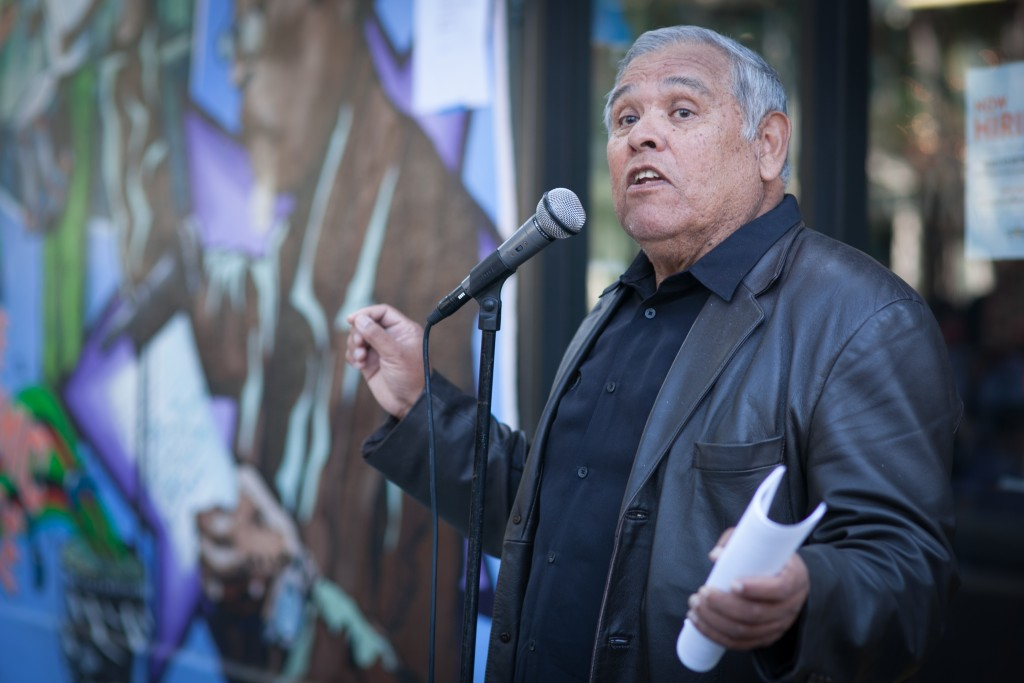 The founder of El Tecolote newspaper Juan Gonzales speaks to the crowd during the celebration of the mural project, which completed by Precita Eyes Muralists Association and Center at the corner of 24th and Folsom streets, San Francisco on Saturday, Aug. 8, 2015. (Photo by Ekevara Kitpowsong/TheGuardsman)