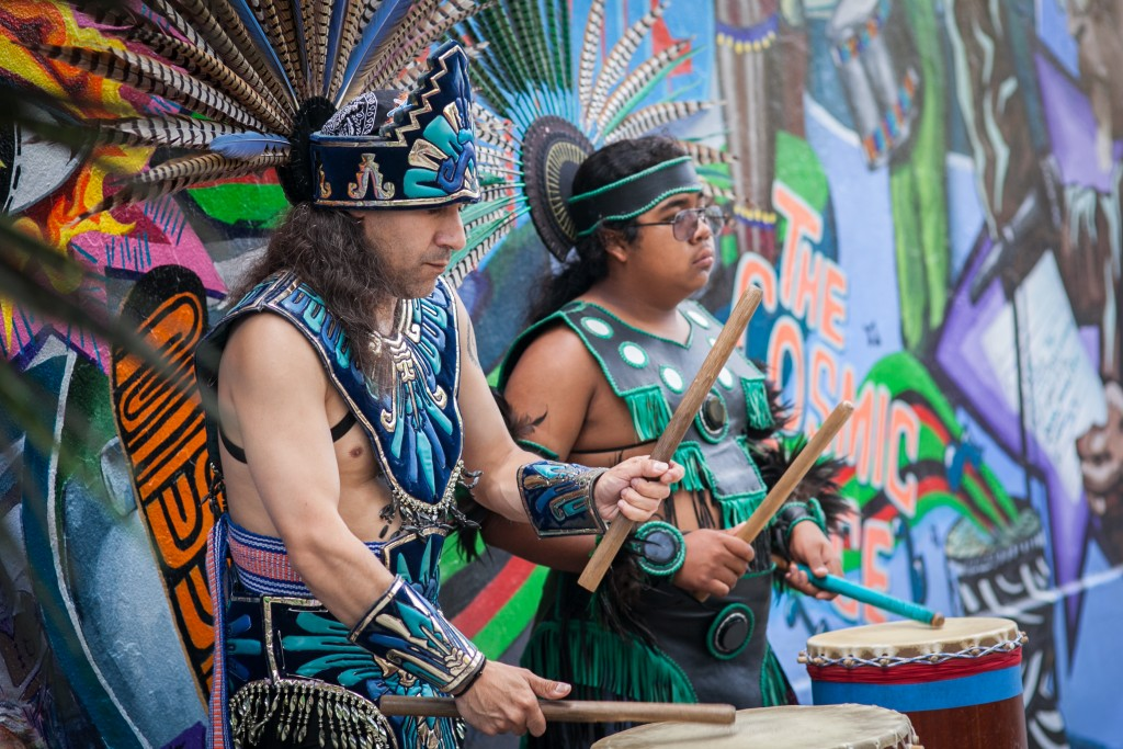 "(L-R) Drumming performance by Bismarck Delgado and Chicome Malinallo (Frank Cortes) during traditional Mexican spiritual dance celebrating the opening of the mural titled ""This Place"" on the corner of 24th and Folsom streets. Saturday, Aug. 8, 2015. (Photo by Ekevara Kitpowsong/TheGuardsman)"
