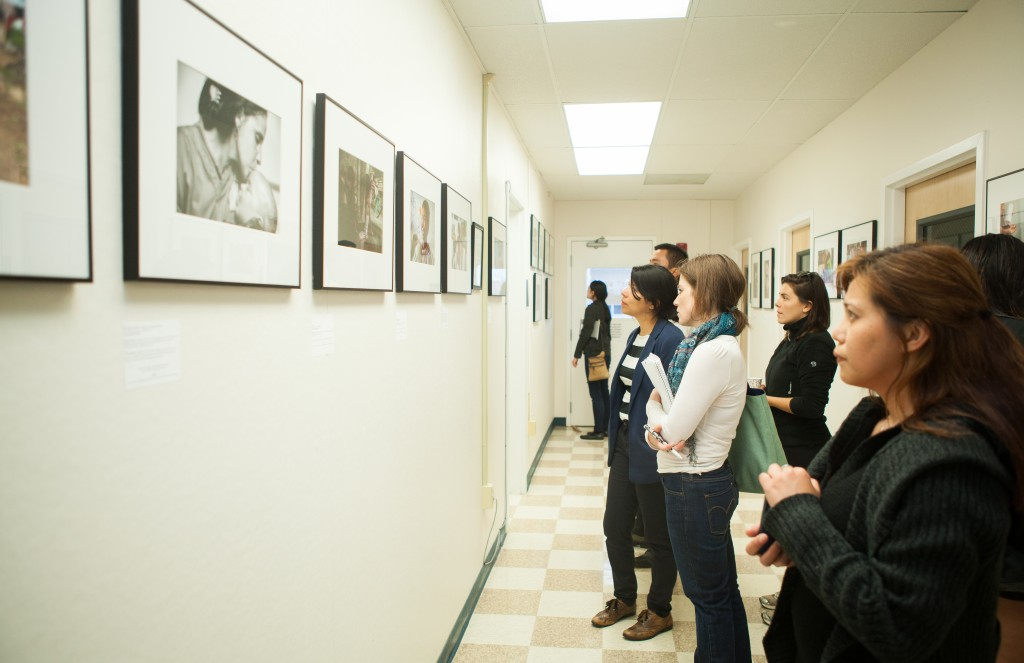 "Guests view photographs of ""Faces of Hope"" exhibition at Front Page Gallery during the opening reception on Thursday, Sept. 17, 2015. (Photo by Ekevara Kitpowsong/The Guardsman)"