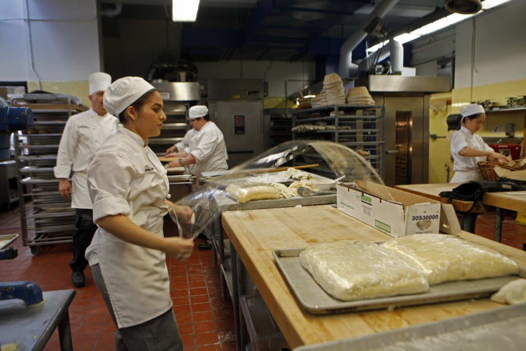 First semester culinary student Lesia Gomez pulls out cellophane to cover the pastry dough. (Photo by Franchon Smith/ The Guardsman)