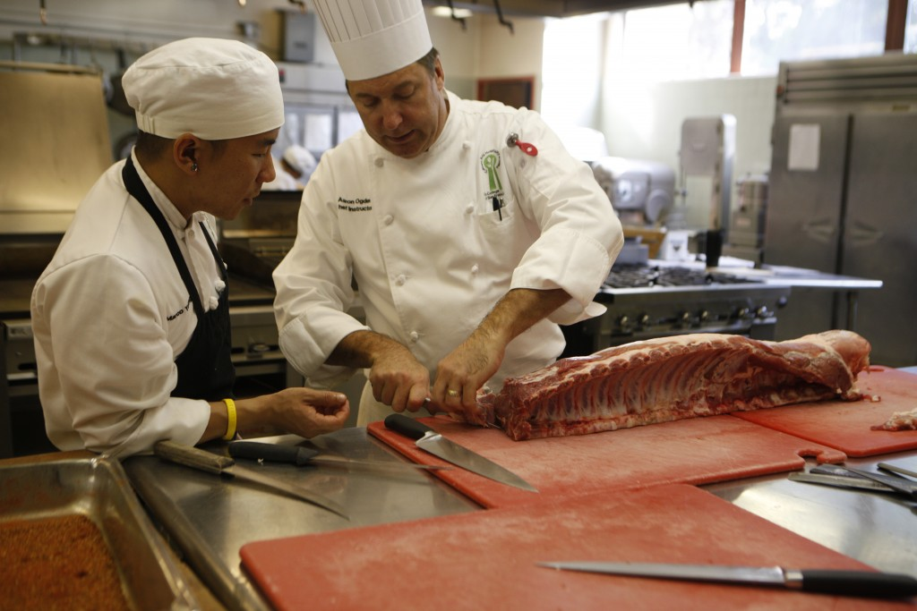 Chef Aaron Ogden, right, shows second-semester culinary student Marco Young how to cut beef sections. (Photo by Franchon Smith/ The Guardsman)