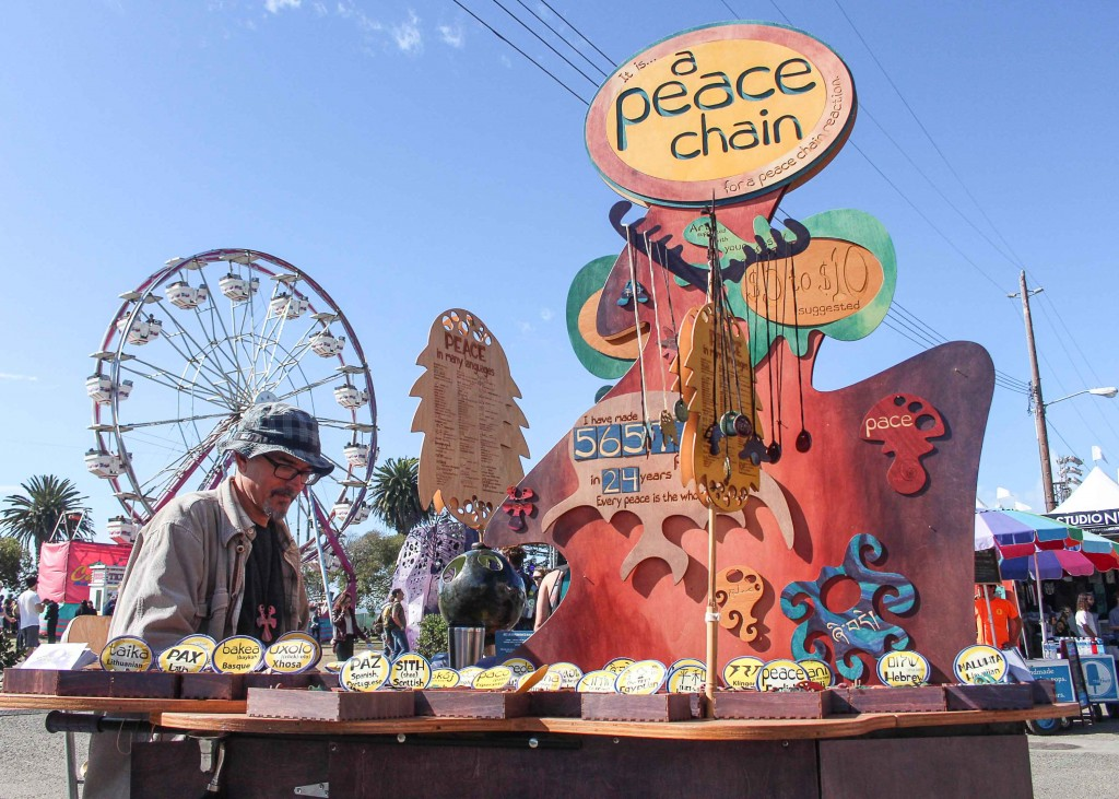 "Joe Murphy a.k.a Joe Peace, a creator of The Peace Chain, sets up his booth at the festival. Peace has crafted 570 clay pendants and multiple works with words for ""Peace"" in different languages for more than 24 years. (Photo by Calindra Revier/The Guardsman)"