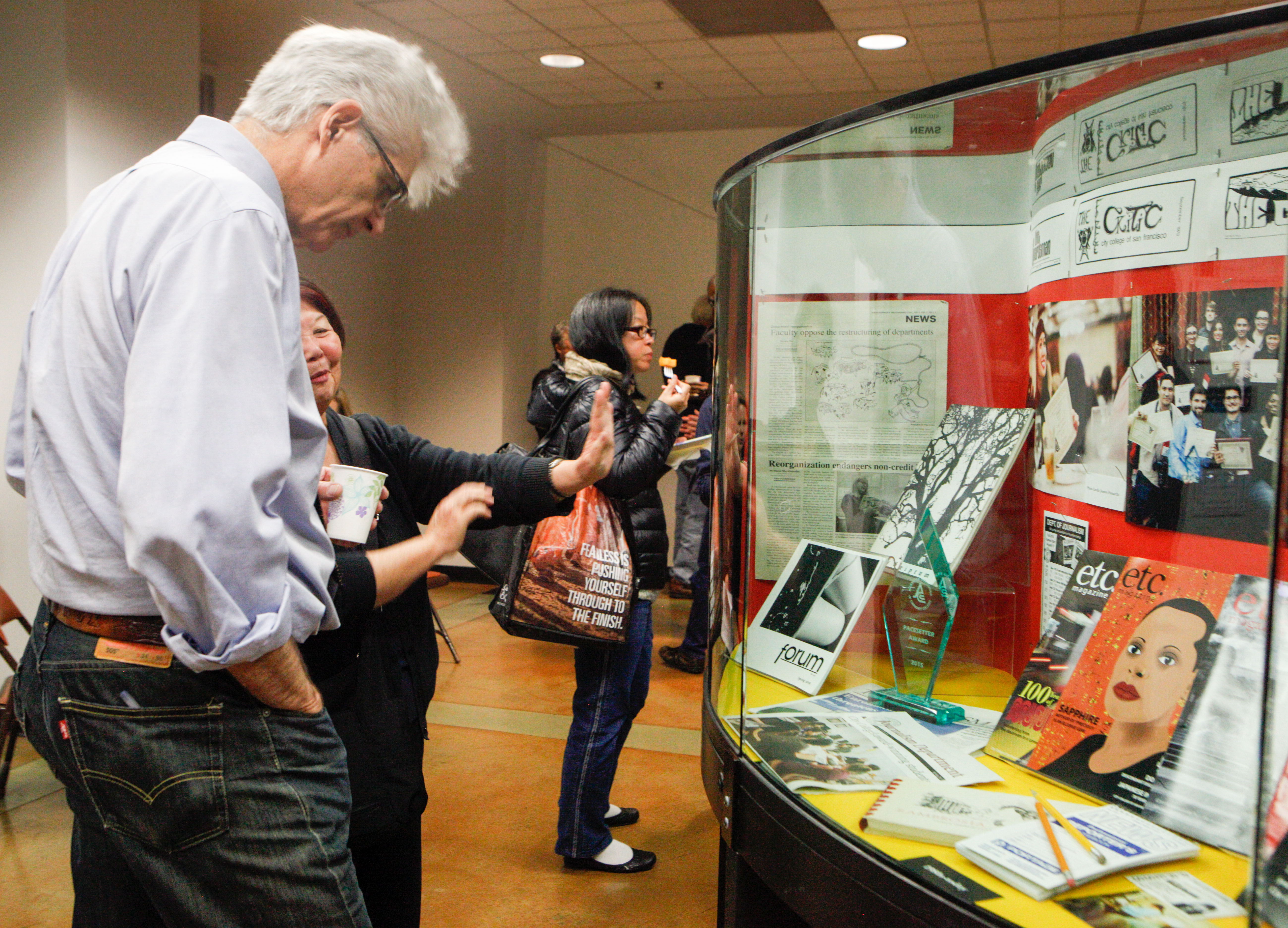 Attendees of the 80th Anniversary celebration of City College's newspaper, The Guardsman, view photos and historical information on display in the Rosenberg Library on Thursday Nov. 12, 2015. (Photo by Fran Smith/ The Guardsman)