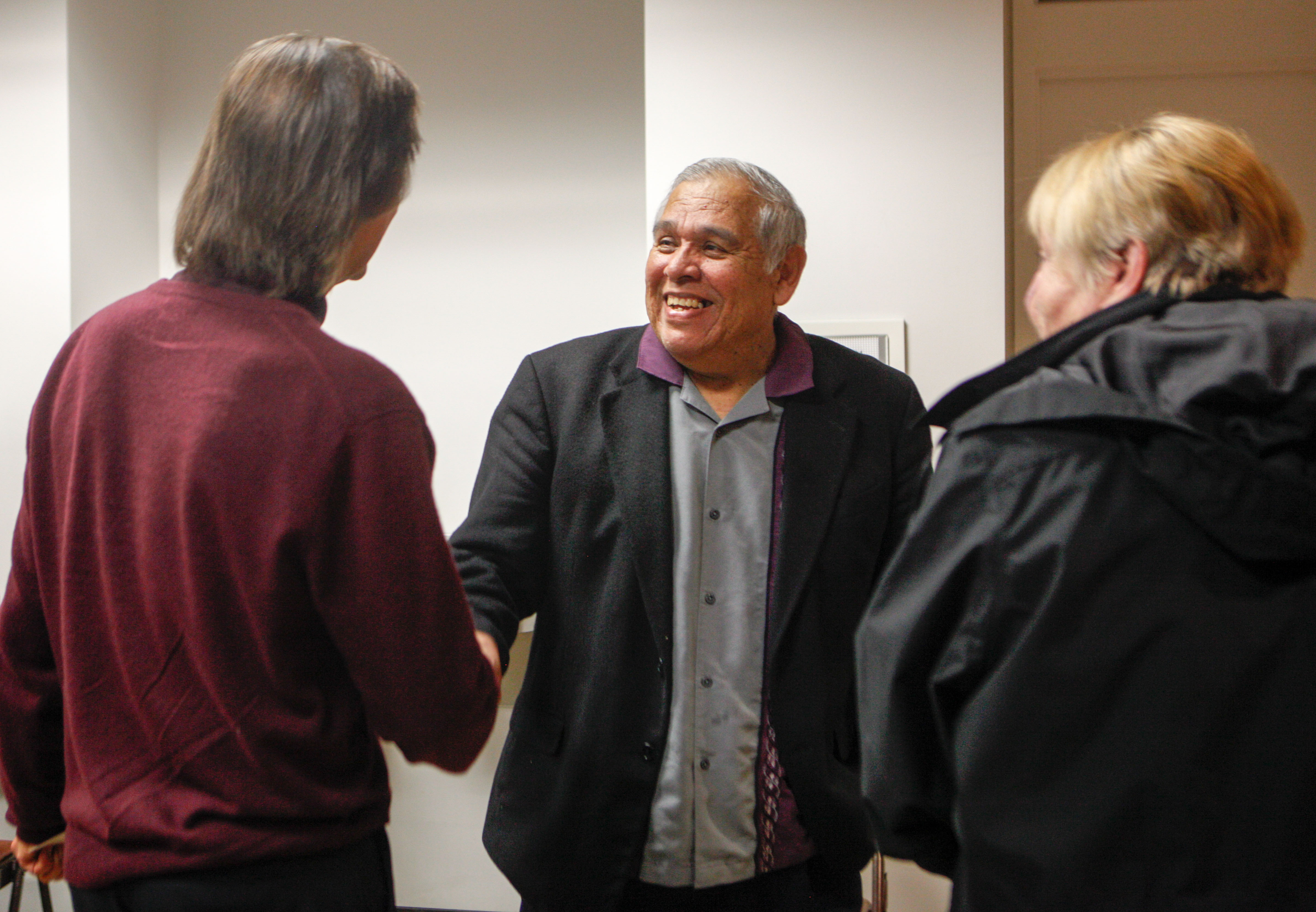 Journalism department chair and The Guardsman advisor, Juan Gonzales, greets guests, left, ESL instructor Victor Turks and retired CCSF librarian Julia Bergman, right, at the 80th Anniversary celebration of the colleges newspaper on November 12, 2015 at the Louise & Claude Rosenberg, Jr. Library. (Photo by Franchon Smith/The Guardsman)