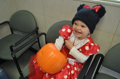 Chanel, dressed as Minnie Mouse, reaches into her basket for more candy at the Extended Opportunity Programs and Services building while trick-or-treating.