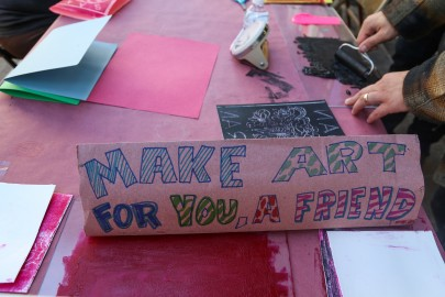 "A sign reading ""Make art for you, a friend,"" rests on the table inviting people in downtown San Francisco to sit and create artwork."