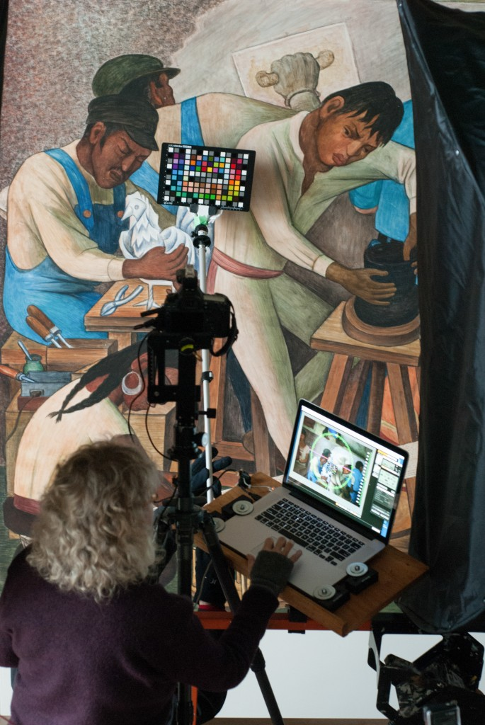 Carla Schroer of the non-profit, Cultural Heritage Imaging, setting up the laptop and camera so she can scan the Diego Rivera Mural located in the Diego Rivera Theater at the main campus in San Francisco. (Photo by Franchon Smith/ The Guardsman)