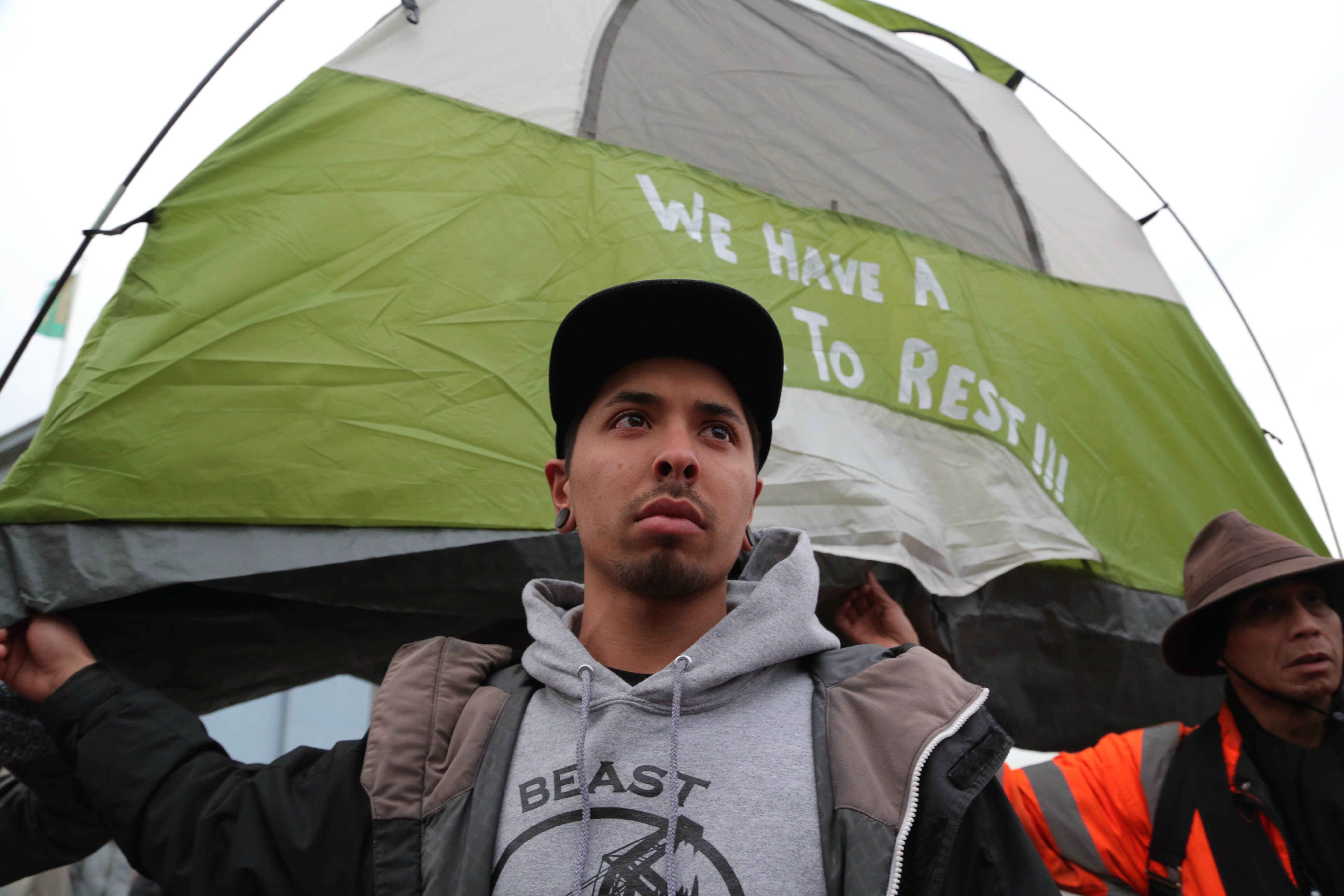 Angelo Chavez holds up a tent to prevent from being cited by police officers during a protest outside Super Bowl City. (Photo by Gabriella Angotti-Jones)