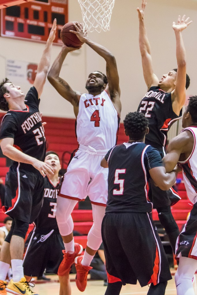Sophomore guard Shon Briggs (4) weaves through four Foothill College defenders on his way to the net for a layup. (Photo by Peter Wong/Special to The Guardsman)