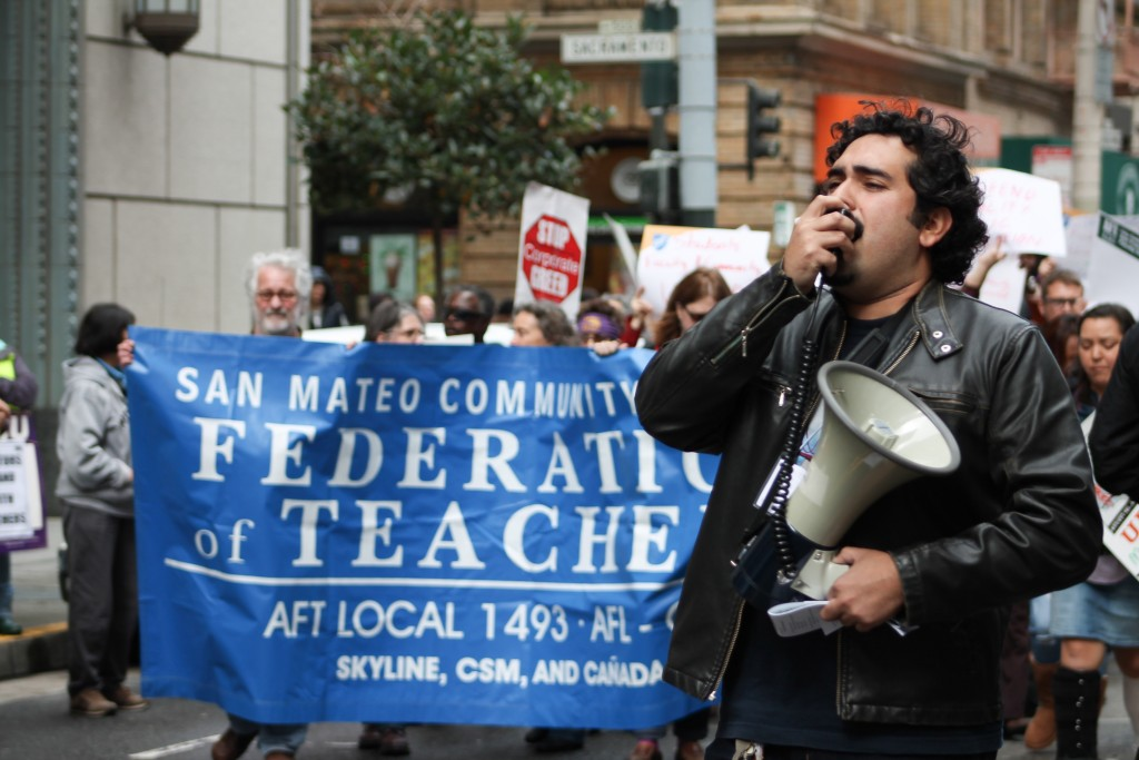 A protester calls for higher quality public education through his megaphone as faculty, students, and community members march around him on March 11, 2016. (Audrey Garces/The Guardsman)