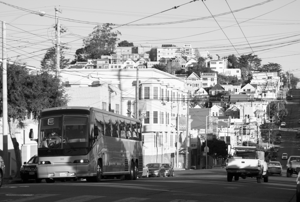 """The large, unmarked """"tech bus"""" drives through a neighborhood in San Francisco. Tech buses have become symbols of the tech invasion in the city. (Photo courtesy of Don Barret/Flickr.com)"""