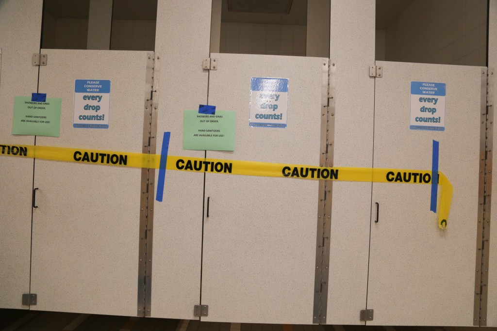 Caution tape marks off Wellness Center bathroom stalls after a leak was caught in a room adjacent to the water system on april 11, 2016. (Photo by Gabriella Angotti Jones/The Guardsman)