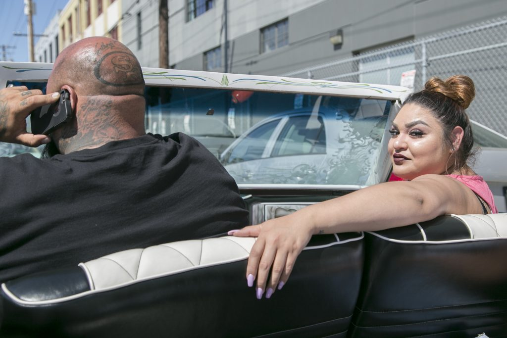 Karla Alarco glances behind her from the passenger seat of a lowrider car outside the car show. (Photo by Gabriella Angotti-Jones).
