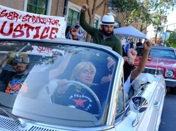 """The """"Frisco Five,"""" a group of people on hunger strike outside the Mission Police Station, are cheered on by lowrider drivers and supporters, Sunday, May 1, 2016 in San Francisco, Calif. Maria Cristina Gutierrez, age 66, is seen at the wheel with her 42-year-old son Ilych Sato to her right. Edwin Lindo, age 29, is seen sitting on top of the car and to his left, Sellassie Blackwell, 39, and 42-year-old Ike Pinkston (to Lindo's right). (Photo by Santiago Mejia/ special to The Guardsman)"""