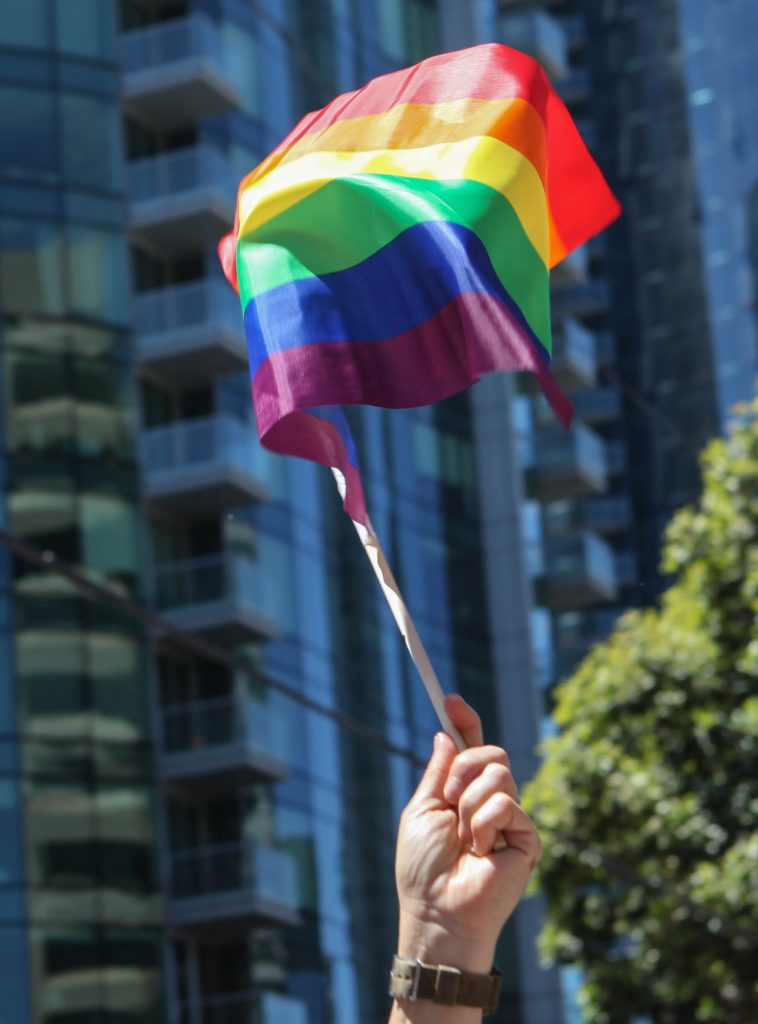 Board of Trustee Vice President, Thea Selby holds a rainbow pride flag before the start of the San Francisco Pride Parade on June 26, 2016. (Photo by Cassie Ordonio/The Guardsman)