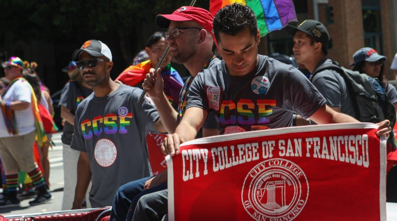 City College Board of Trustee member Alex Randolph displays a City College banner while Board of Trustee President Rafael Mandelman holds a pride flag while waiting for the San Francisco Pride Parade to begin on June 26, 2016. (Photo by Cassie Ordonio/The Guardsman)