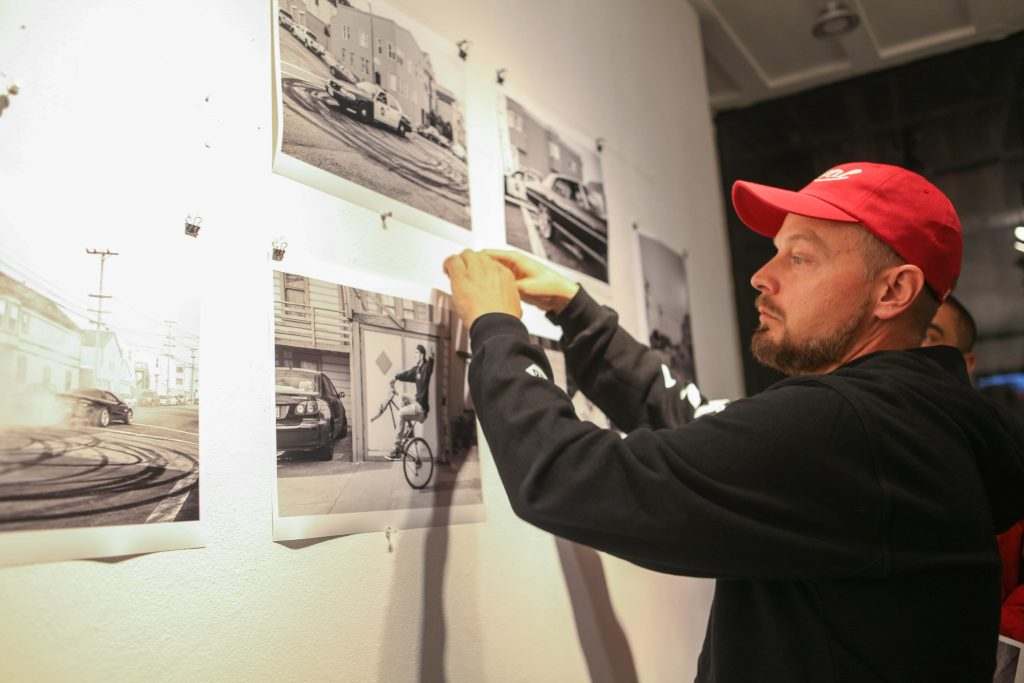 Travis Jensen gives away photographs to his supports at Book and Job gallery on Aug. 5, 2016 (Photo by Cassie Ordonio/The Guardsman)
