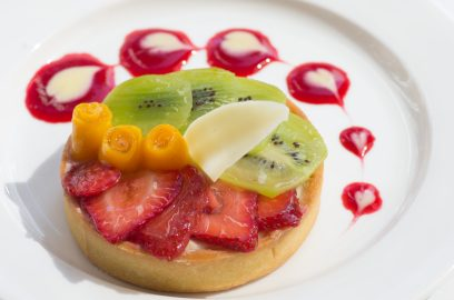 The Educated Palate served a fresh fruit tart with sliced strawberry and kiwi topped with mango flowers on its Sept. 28 dessert menu. White chocolate hearts garnish the plate atop fruit sauce. (Photo by David Horowitz/The Guardsman)