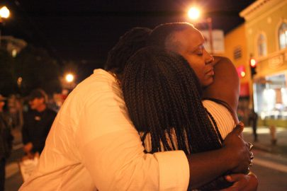 Mustafah Grenne (right), Tiara J (middle) and April Martin (right) share a hug after their performance at the intersection of 22nd and Mission St on Nov. 3, 2016