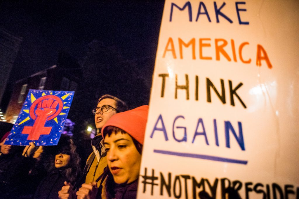 "A woman bobs sign reading ""Make America think Again, ""while protesting against, ""#notmypresident,"" during inagural march Ja. 20, 2017. (Photo by Gabriela Reni/The Guardsman)"