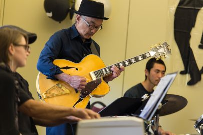 """Katsumi Asazawa, center, plays a guitar solo during the band's performance of """"Saint Louis Blues"""" by W.C. Blues in the Pierre Coste Room on Apr. 13, 2017. Photo by John Ortilla/The Guardsman."""