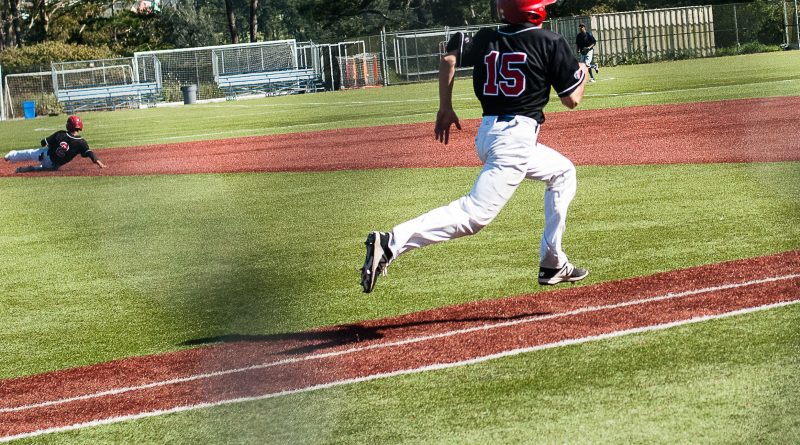 Rams pitcher Jesse Navarro sprints to first base while Matt Schivo slides into second. Photo by Otto Pippenger, April 20 2017, Pacifica.