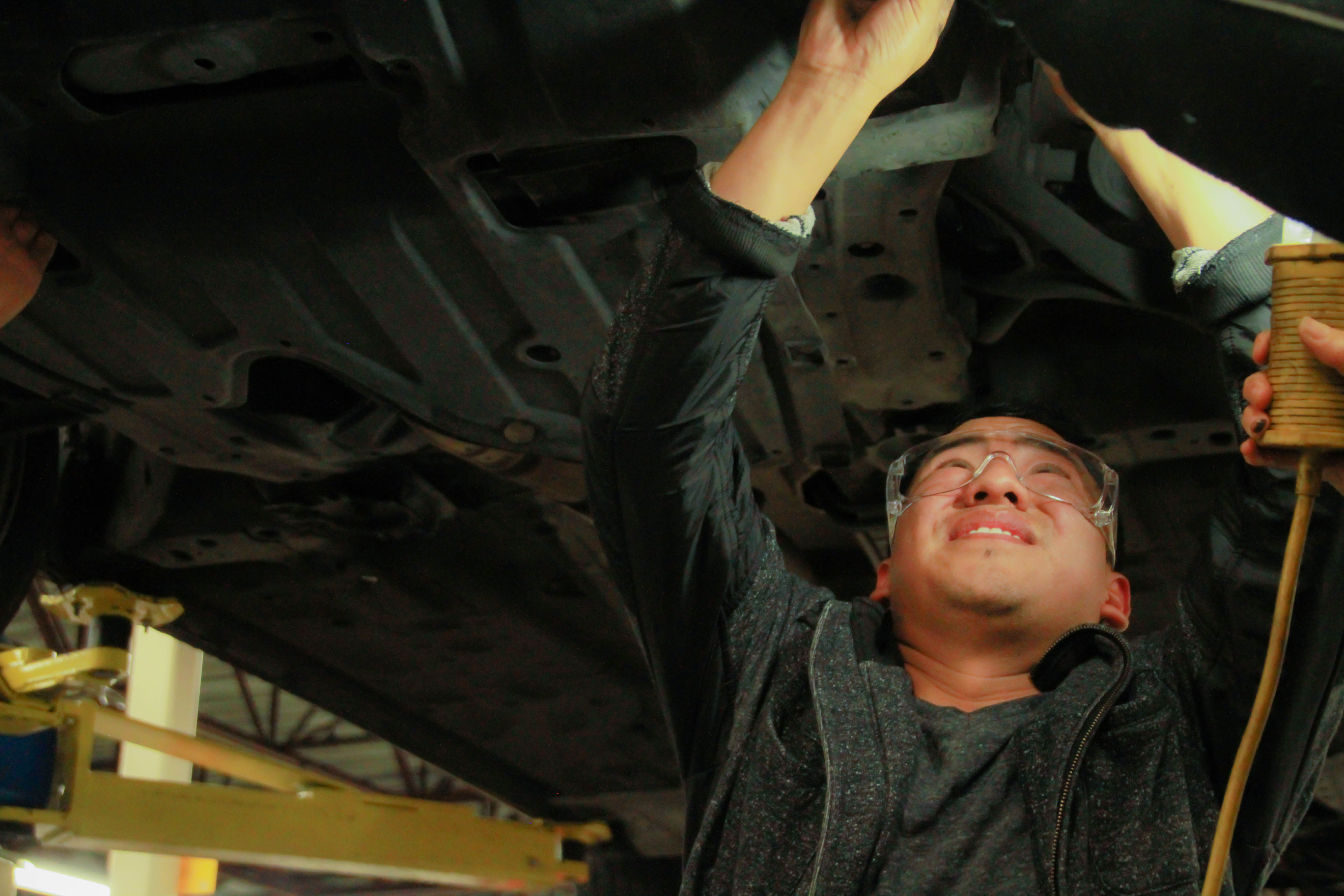 Byron Mejia, 28, works on his car at the City College Evans Campus during an automotive course that teaches students basic auto maintenance. Photo by Karen A Sanchez/The Guardsman