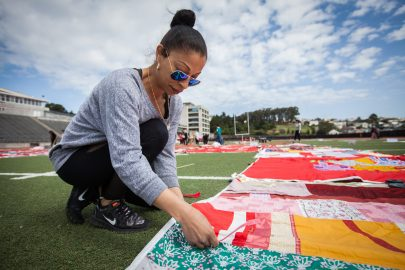 A volunteer, Alexis Ortiz, City College of San Francisco Women's Studies student helps set up during the installation of The Monument Quilt on the football field of George M. Rush Stadium at City College of San Francisco Ocean Campus on Saturday, May 6, 2017.  (Photo by Ekevara Kitpowsong)