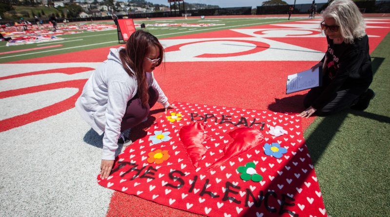 (L-R) An instructor of Ending Sexual Violence: Peer Education Shella Cervantes and Interim Project SURVIVE Coordinator Leslie Simon display a red quilt made by a City College of San Francisco student during an installation of The Monument Quilt on the football field of George M. Rush Stadium at City College of San Francisco Ocean Campus on Saturday, May 6, 2017.  (Photo by Ekevara Kitpowsong)